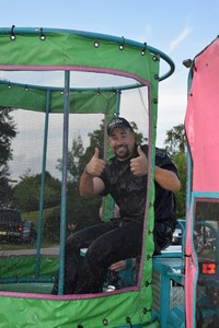 Police officer giving thumbs up while sitting on dunk tank at national night out event