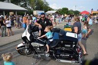 Police officer letting a little boy sit on his motorcycle at national night out event
