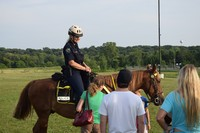Police officer giving horseback demonstration at national night out event